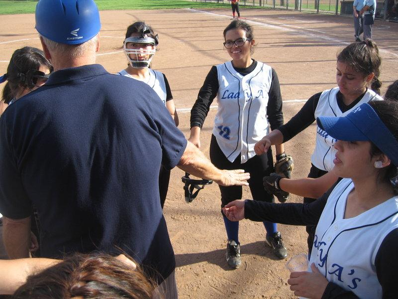 The Lady A's huddle up with their coach, Mr. Dura, before a game. Photo provided by Mr. Dura.