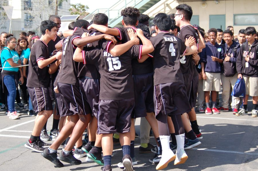 The boys volleyball team huddle together to say their chant.
